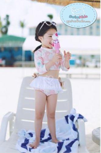 ชุดว่ายน้ำเด็กหญิงแขนยาวสีชมพูอ่อนลายดอกไม้ขาว โชว์เอว พร้อมกางเกงกระโปรง ตกแต่งโบว์
